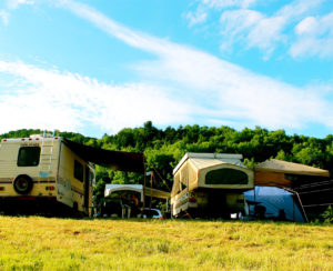 RVs and campers set up along the woodsline with beautiful sunshiny skies.